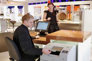 Hier bekommt eine junge Dame ihr Geld am Bankschalter.