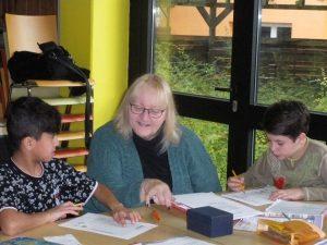Ehrenamtliche Mitarbeiterin des MGH bei der Hausaufgabenhilfe mit Flüchtlingskindern der Übergangsklasse in der Mittelschule Röthenbach. Foto: Caritas